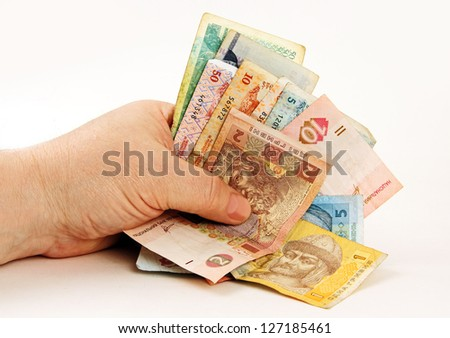 man's hand holding several banknotes of different countries.