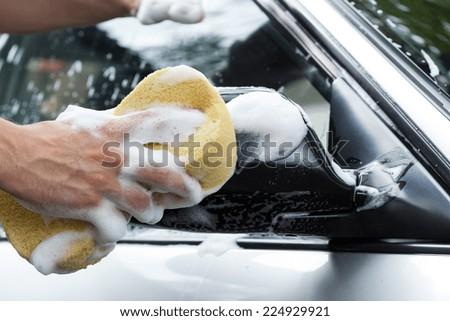 Man's hand holding sponge full of foam - stock photo