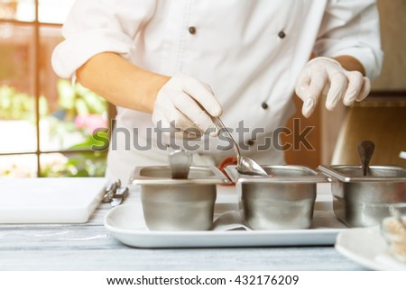 Man's hand holding spoon. Spoon next to sauce containers. Chef chooses flavor for meat. Professional cook at work. - stock photo