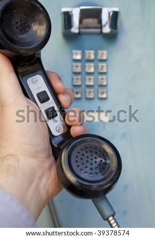 man's hand holding the handset of a public telephone, with selective focus on volume adjustment buttons - stock photo