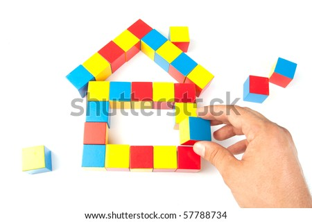 Man's hand holding wooden block. Building a house - stock photo