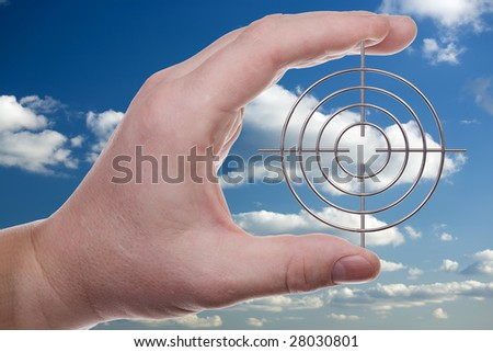 Man's hand holds a target on a background of the sky with clouds. With clipping path. - stock photo
