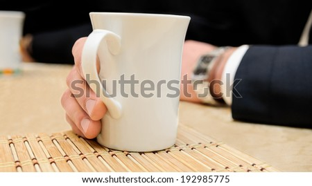 man's hand holds cup of a hot drink as tea or coffee on the table - stock photo