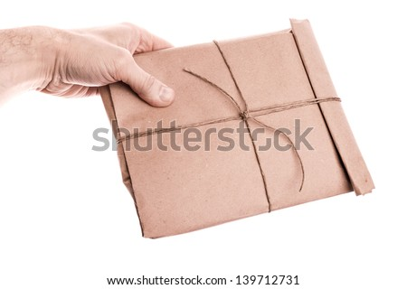 Man's hand holds envelope tied with a rope isolated on white - stock photo