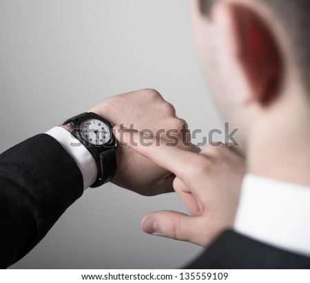 Man's hand in the suit pointing on his watch on a gray background - stock photo