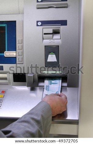 man's hand inserting banknote into cash dispense - stock photo
