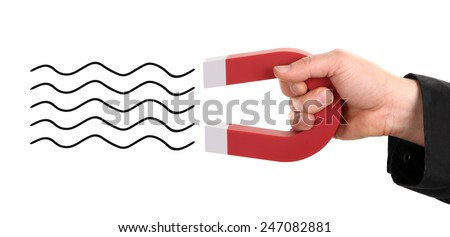 Man's hand is attracting something with horseshoe magnet - stock photo