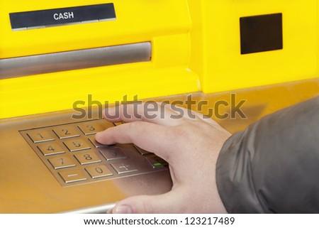 Man's hand near the cash machine on the pin code - stock photo