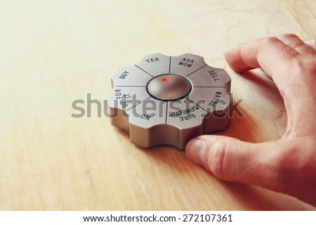 man's hand next to decision maker office gadger. business and desicion making concept. image is retro filtered - stock photo