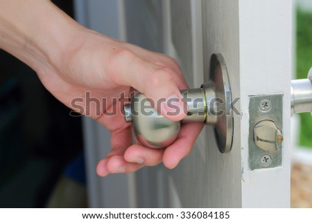 man's hand open the white door - stock photo