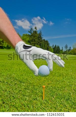 Man's hand placing golf ball on the tee. - stock photo