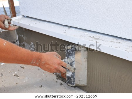 Man's hand plastering a wall insulation with trowel.
