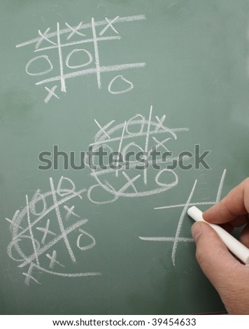 Man's hand playing a game of tic tac toe on a chalkboard.