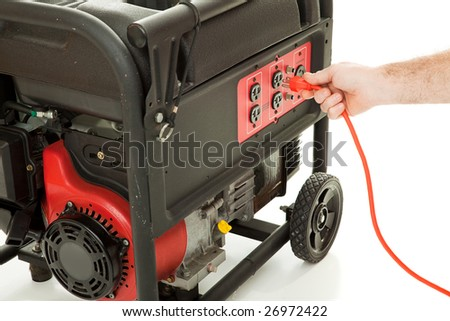 Man's hand plugging an extension cord into an emergency generator. - stock photo