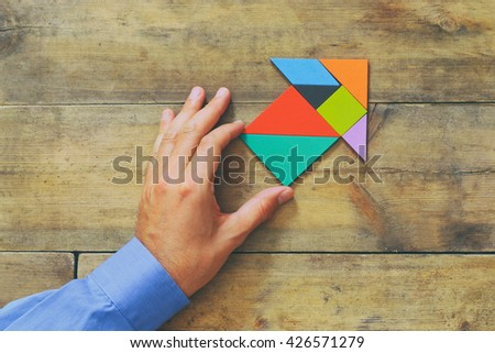 man's hand pointing at arrow made from square tangram puzzle, wooden background  - stock photo