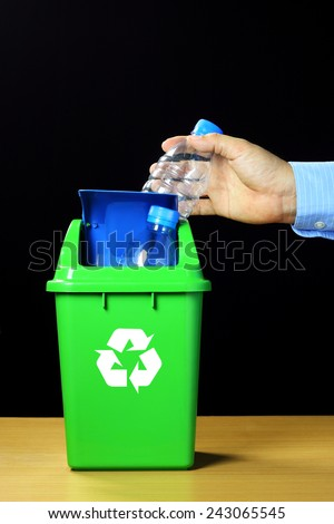 Man's hand putting a plastic bottle into a recycling bin. - stock photo