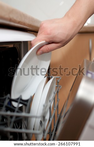 Man`s hand putting a plate in the dishwasher. Housework. - stock photo