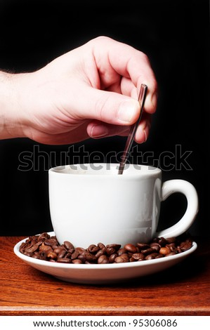 man's hand putting a spoon in a coffee cup - stock photo
