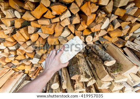 man's hand putting log into the stack of firewood - stock photo