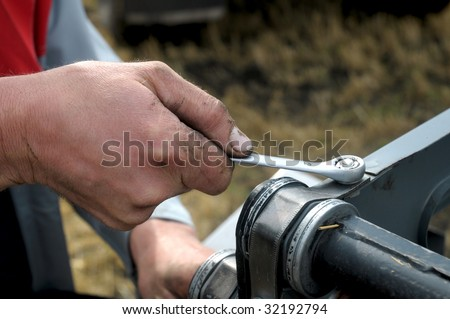 man's hand reapiring harvester whith wrench on field - stock photo