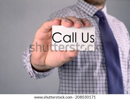 Man's hand showing business card with text Call Us - closeup shot on grey background  - stock photo