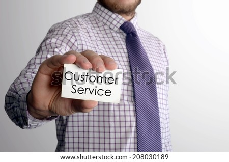 Man's hand showing business card with text Customer Service - closeup shot on grey background  - stock photo