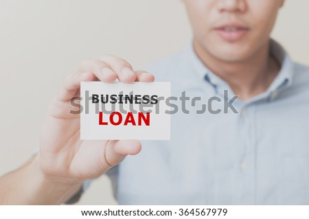 Man's hand showing BUSINESS LOAN on the card business card - closeup shot on white background. - stock photo