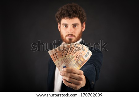 Man's hand showing euros banknotes against black background. Focus on banknotes. - stock photo
