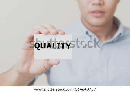 Man's hand showing QUALITY text on the card business card - closeup shot on white background. - stock photo