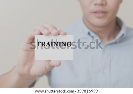Man's hand showing TRAINING on the card business card - closeup shot on white background