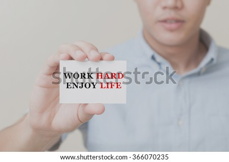Man's hand showing Work Hard Enjoy Life text on the card business card - closeup shot on white background. - stock photo