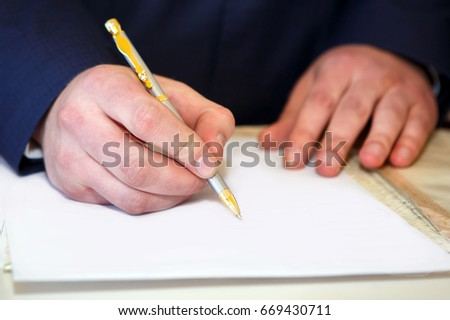 Man's hand signing a contract on paper with a pen. Business meeting at the table. Important documents for signature.