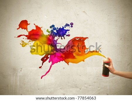 Man's hand spraying colored paint - stock photo