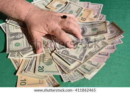 Man's hand squeezes dollar bills Greedy man's hand with a finger ring on the finger squeezes dollar bills   - stock photo