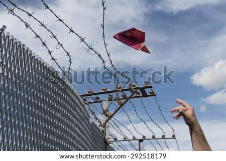 man's hand throwing his passport folded as a paper airplane over a barbed wire fence,  blue sky and copy space - stock photo