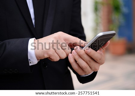 Man's hand touching screen on a smart phone - stock photo