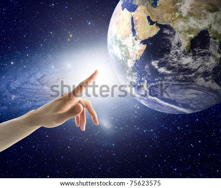 Man's hand touching the Earth - stock photo