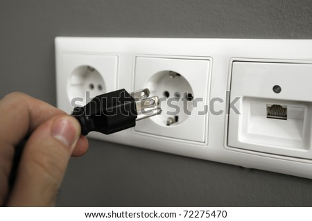 Man's hand trying to plug an american type of plug to an european outlet. This photograph is a great methaphor for for saving electrical energy worldwide - stock photo