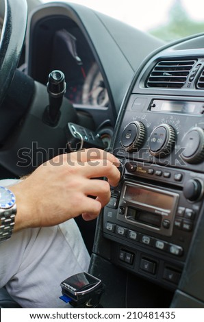 Man's hand tuning radio in the car. - stock photo