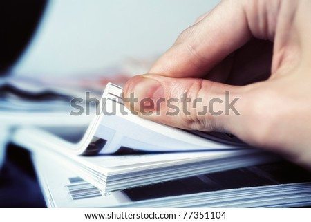 Man's hand turned over a stack of magazines closeup - stock photo