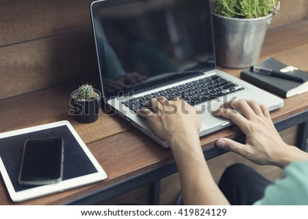 man's hand typing on laptop computer with smartphone and digital tablet on wooden table, selective focus and vintage tone - stock photo