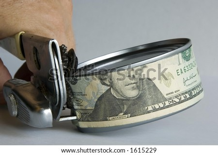 Man's hand using can opener to open a can of money - stock photo