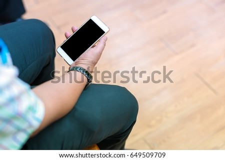 man's hand using smart phone with blank screen on wooden background at home.