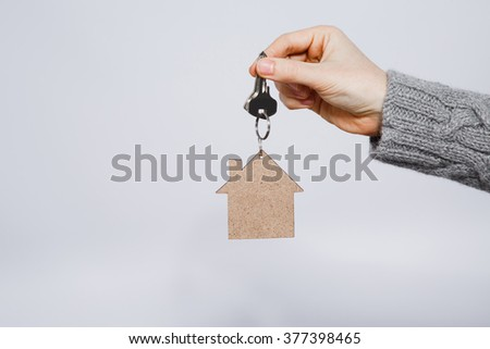 Man's hand wearing warm gray sweater holding little wooden house and keys at gray studio background, close up, mock up, copy space.