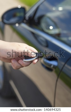 Man's hand with a car alarm remote control - stock photo