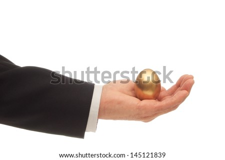 Man's Hand with a Golden Egg Nested in His Palm - stock photo