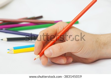 man's hand with a red pencil on the background of pencils - stock photo