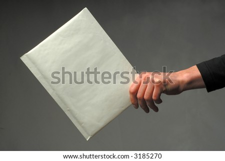 Man's hand with an envelope of white color on  dark background - stock photo