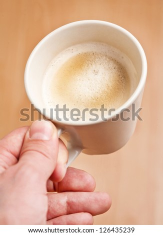 Man's hand with cup of coffee - stock photo