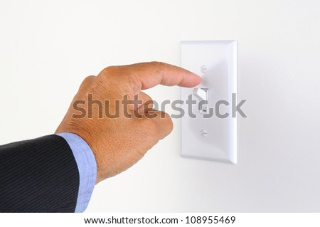 Man's hand with finger on light switch, about to turn off the lights. Closeup of hand and switch only. Horizontal format. - stock photo